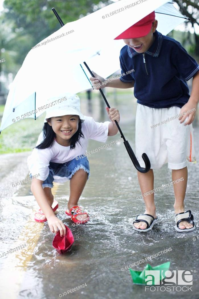Stock Photo: Two young kids outdoors in rain playing with paper boats.