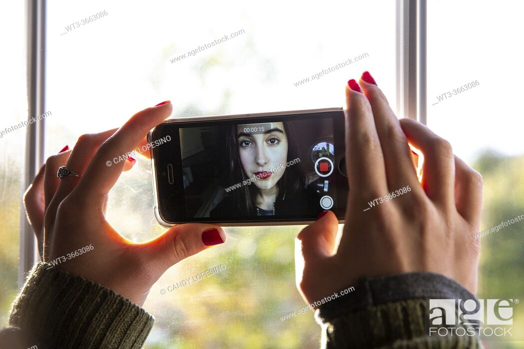 Stock Photo: Young girl recording herself with the mobile phone.