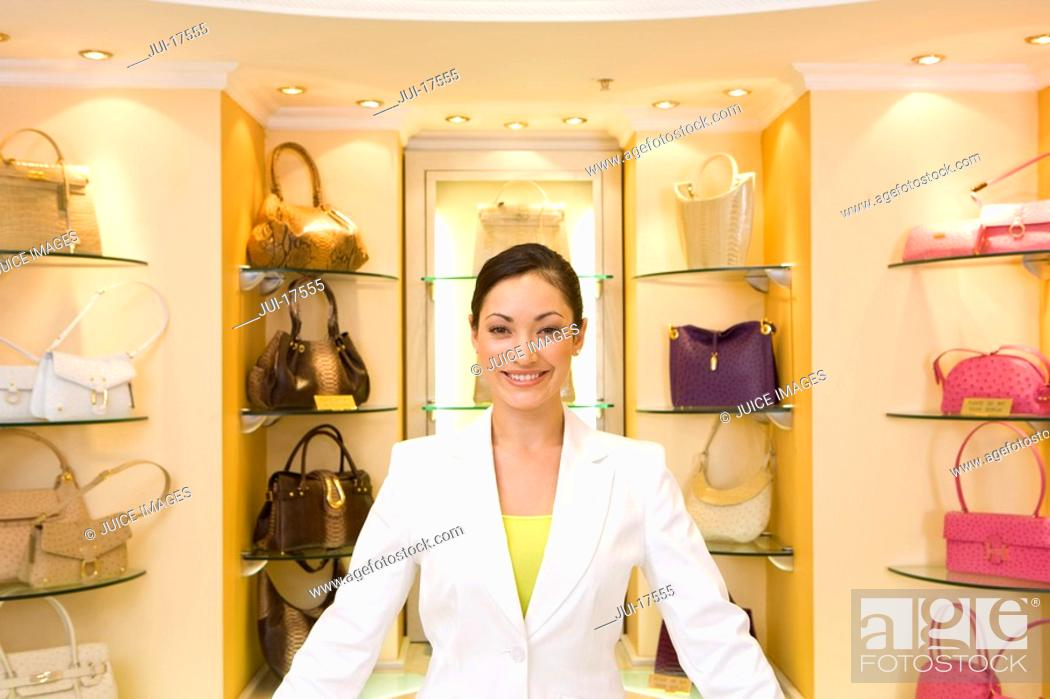 Stock Photo: Saleswoman posing in front of purses.