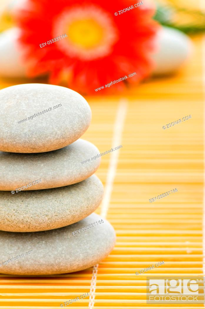 Stock Photo: Red flower and stack of spa pebbles.