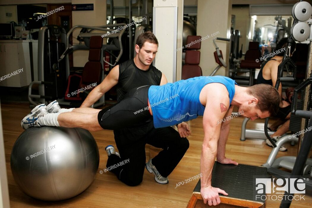 Stock Photo: Men training in gym with instructor showing student moves.