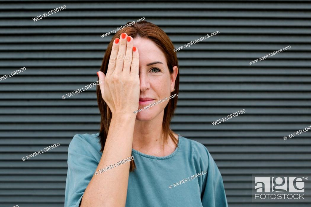 Stock Photo: Woman covering one eye with her hand.