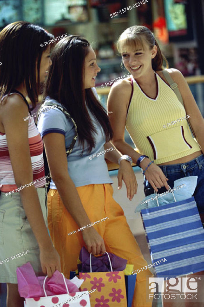 Stock Photo: Side profile of three teenage girls standing with shopping bags.