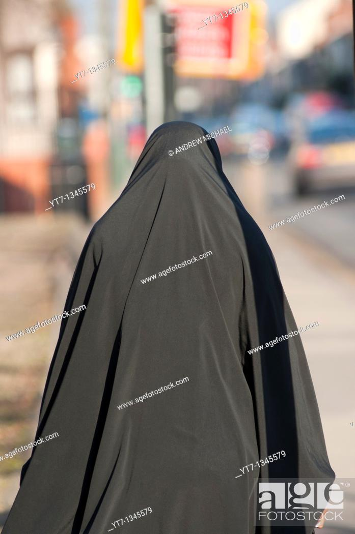 Stock Photo: A Muslim woman wearing a Burka walks down Stoney Stanton Rd in Coventry, West Midlands, England.