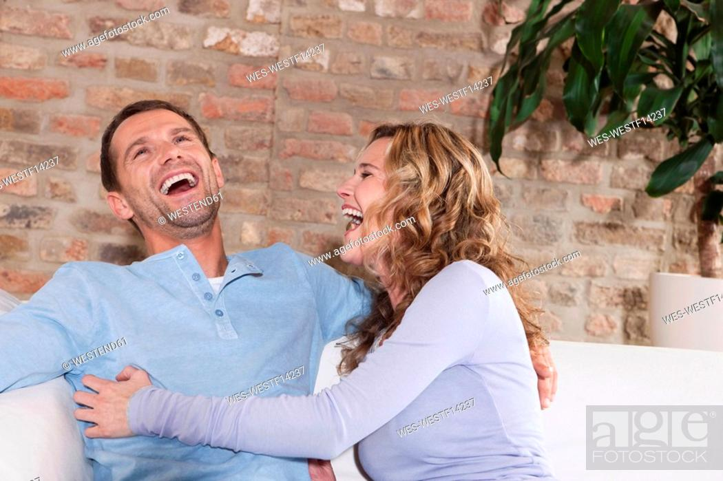 Stock Photo: Germany, Cologne, Couple sitting on sofa, laughing, portrait.