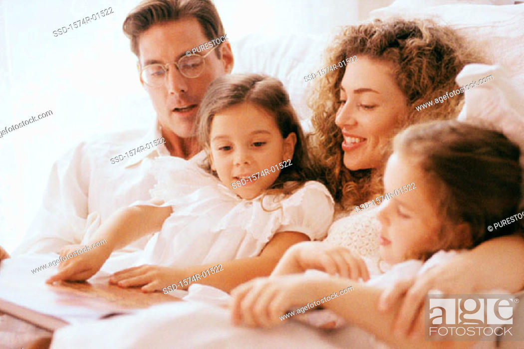 Stock Photo: Parents and their two daughters together in bed.