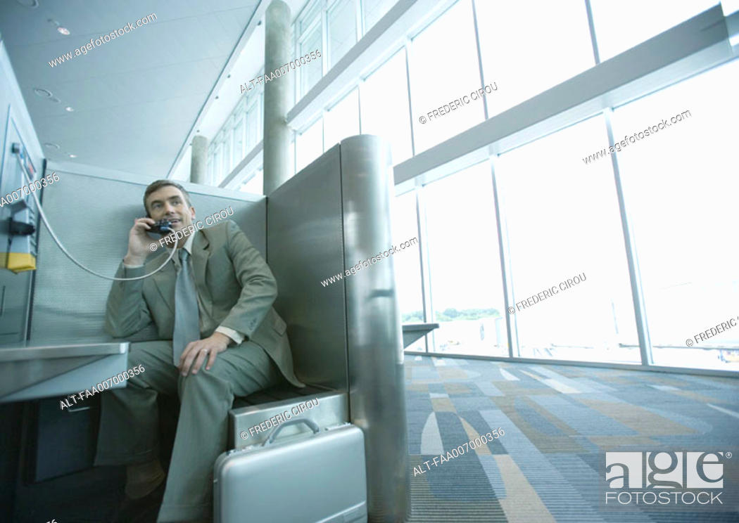 Stock Photo: Businessman using pay phone in airport.