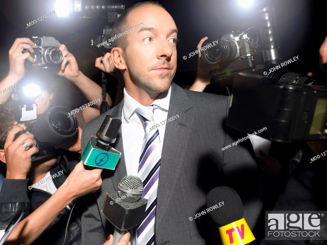 Stock Photo: Man surrounded by paparazzi.