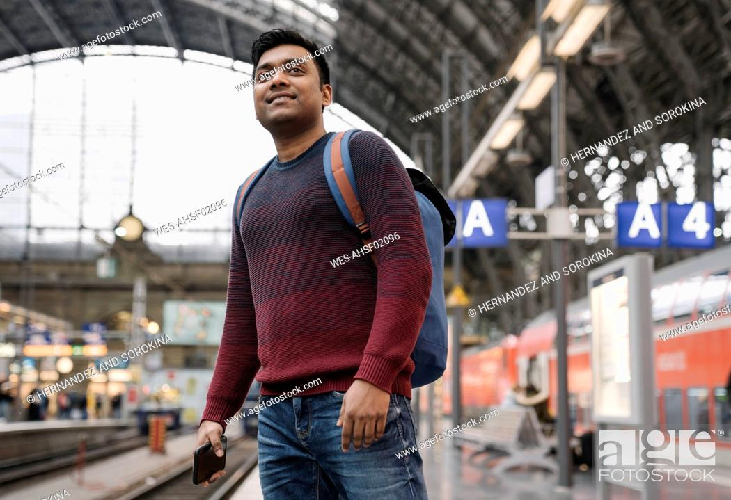 Photo de stock: Man with smartphone waiting for the train at the train station.