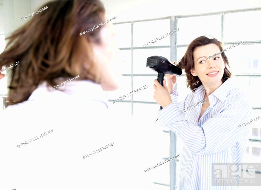 Stock Photo: Woman in mirror applying make up.