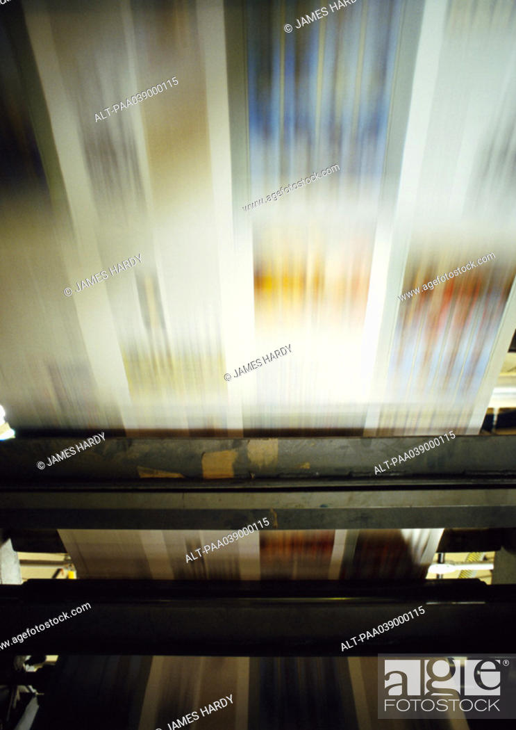 Stock Photo: Printed paper on printing press, blurred motion.