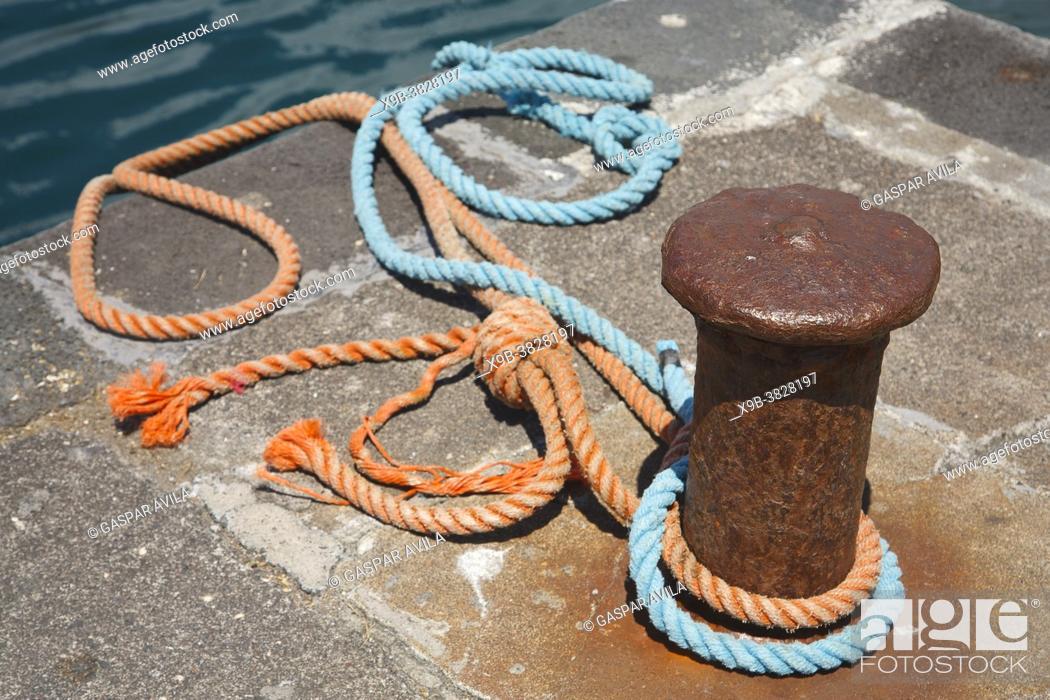 Stock Photo: Mooring bollard and ropes.