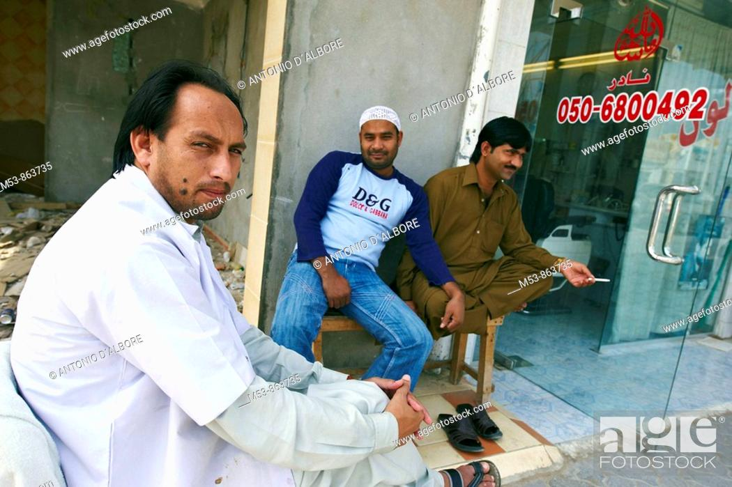 Stock Photo: a pakistani barber wait for customer outside his shop in ras al-khaimah old town  ras al-khaimah  united arab emirates  middle east.