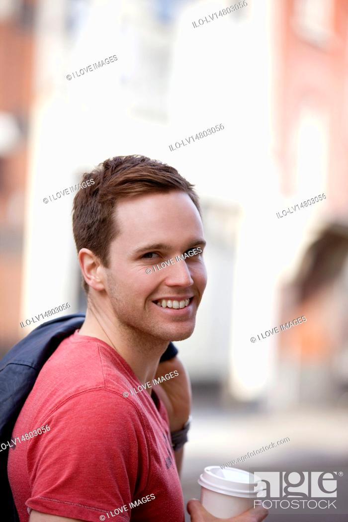 Stock Photo: A young man standing, holding a hot drink.