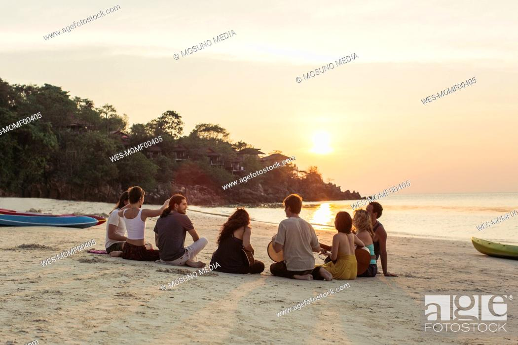Imagen: Thailand, Koh Phangan, group of people sitting on a beach with guitar at sunset.