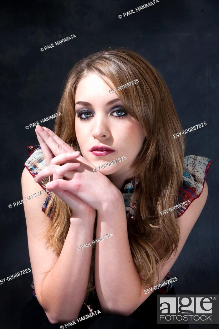 Stock Photo: Beautiful dirty-blond girl sitting with hands together next to her face.
