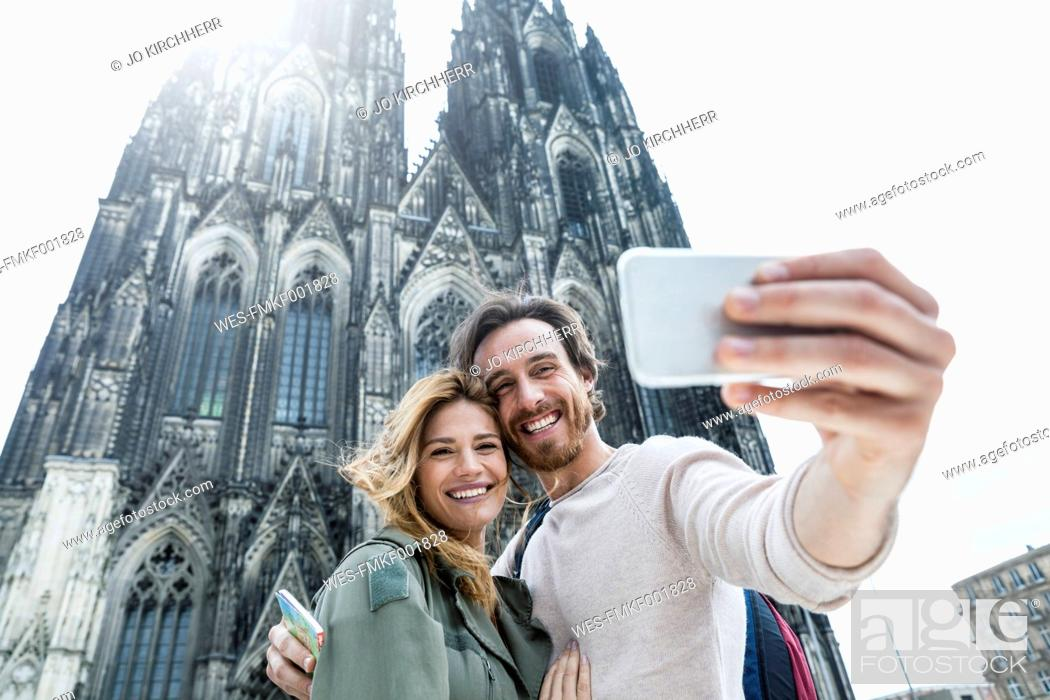 Stock Photo: Germany, Cologne, portrait of young couple taking a selfie in front of Cologne Cathedral.