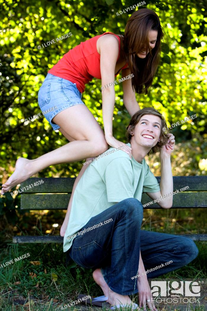 Stock Photo: A young couple having fun on a park bench.