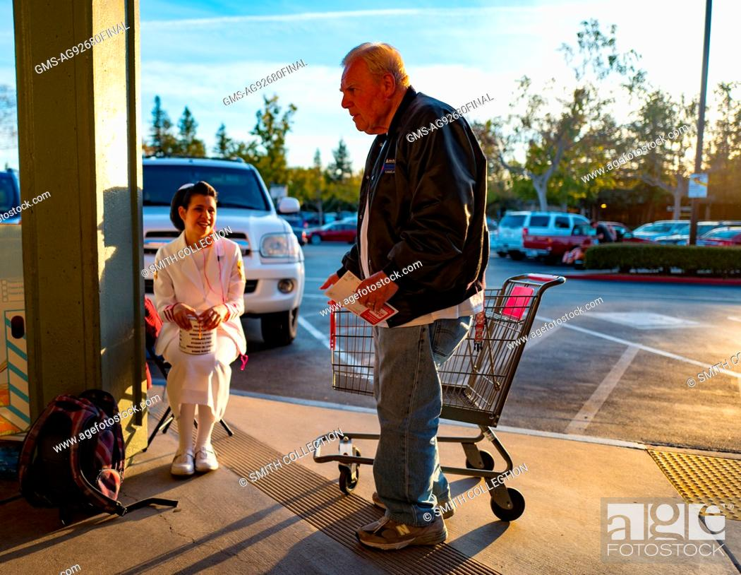a mature man exiting a cvs pharmacy speaks to a young woman in