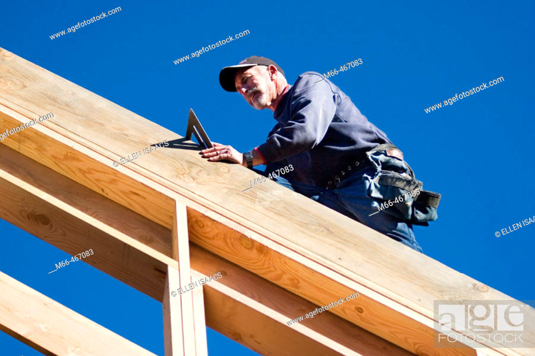 Stock Photo: Carpenter walking along a roof rafter with a speed square at a construction site.
