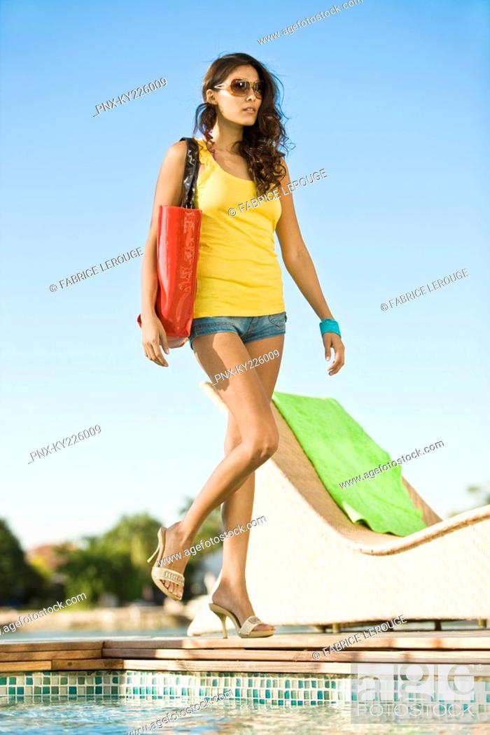 Stock Photo: Low angle view of a woman walking at the poolside.