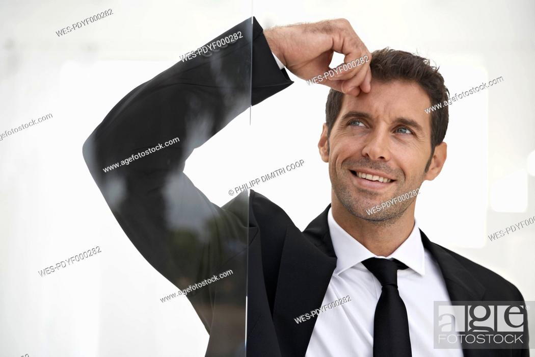 Stock Photo: Spain, Businessman standing by door, thinking.