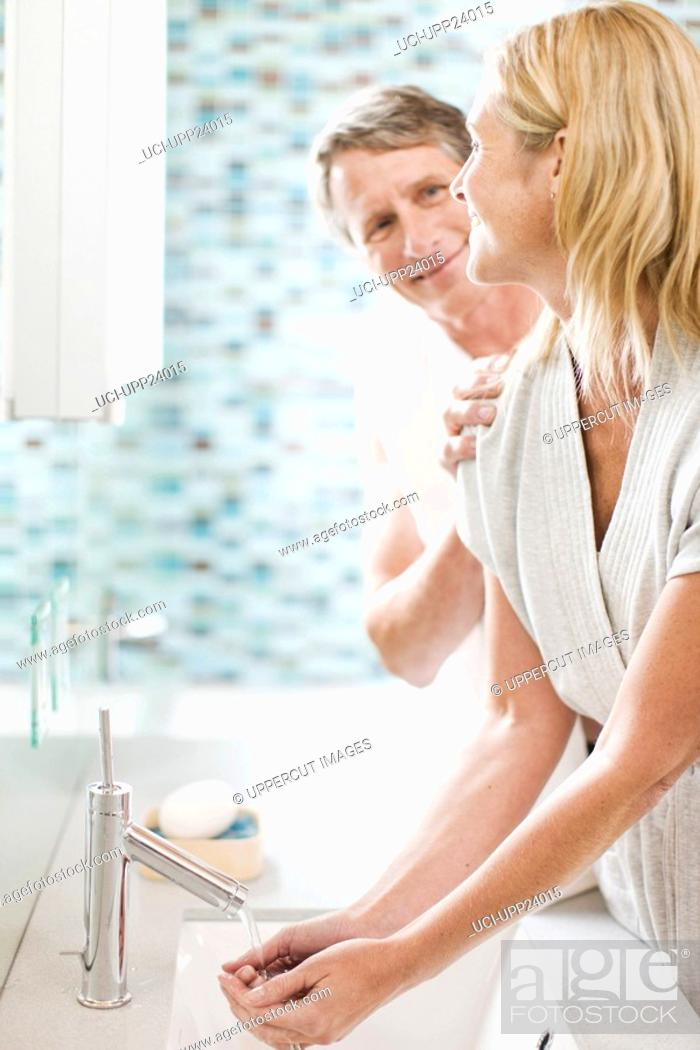 Stock Photo: Man smiling at woman washing hands in bathroom sink.