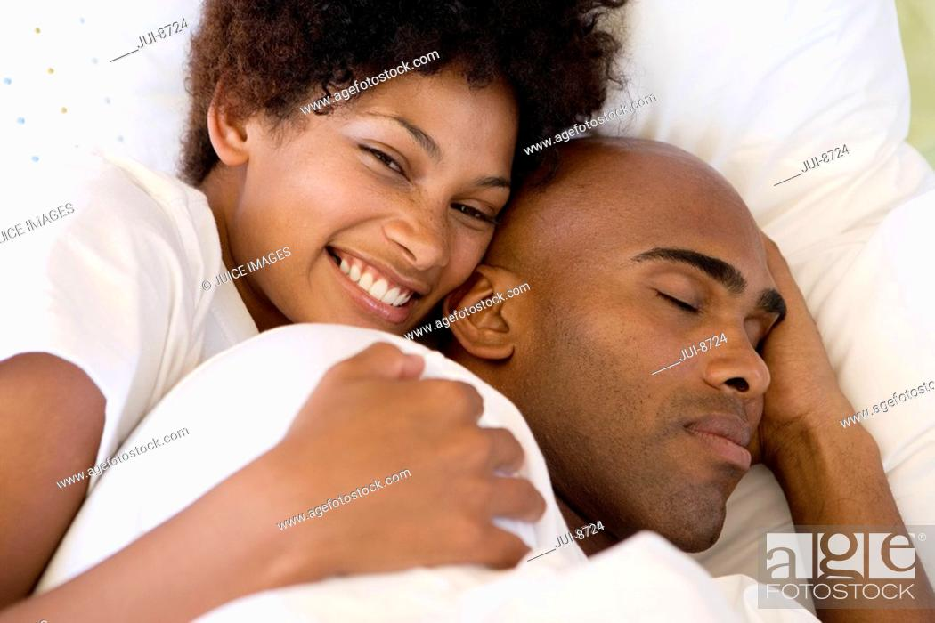 Stock Photo: Young couple lying in bed, woman smiling, portrait, elevated view.