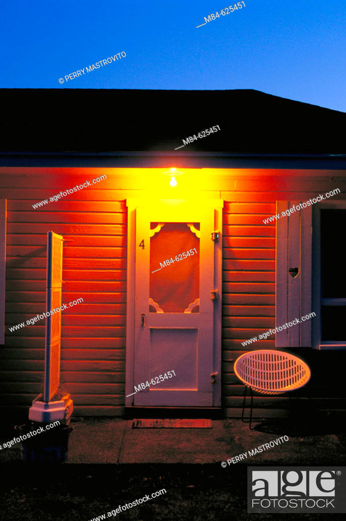 Stock Photo: Illuminated roadside motel room entrance door and porch with chair at dawn.