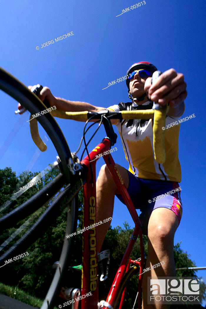 Stock Photo: A young man 15-20 20-25 25-30 years old, sportsman, biker, cyclist, cycling outside in summer.