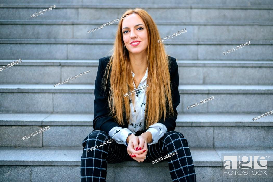 Stock Photo: Portrait of smiling young woman sitting on stairs.