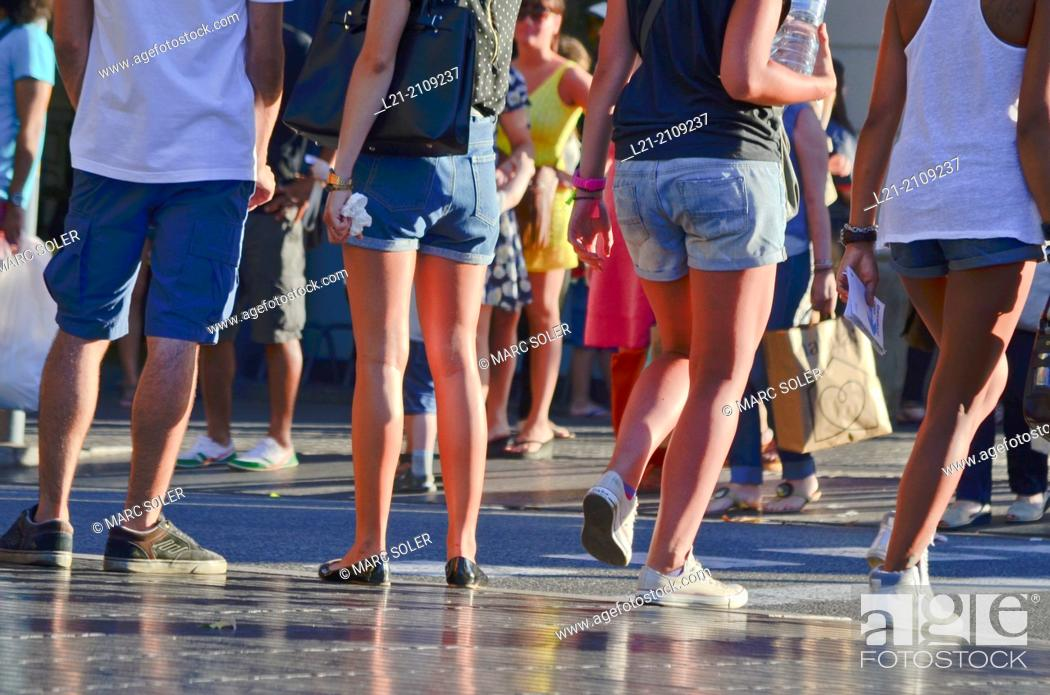Stock Photo: Detail of young legs in shorts in a street, summer. Barcelona, Catalonia, Spain.