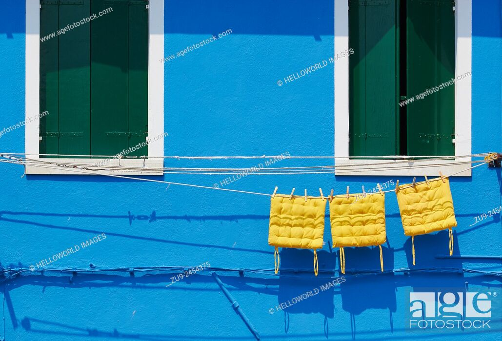 Photo de stock: Three yellow cushions hanging on line outside blue painted house, Burano, Venetian Lagoon, Veneto, Italy, Europe.