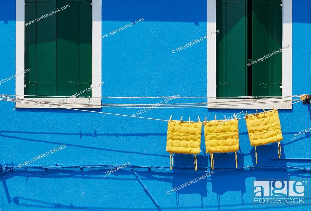 Imagen: Three yellow cushions hanging on line outside blue painted house, Burano, Venetian Lagoon, Veneto, Italy, Europe.