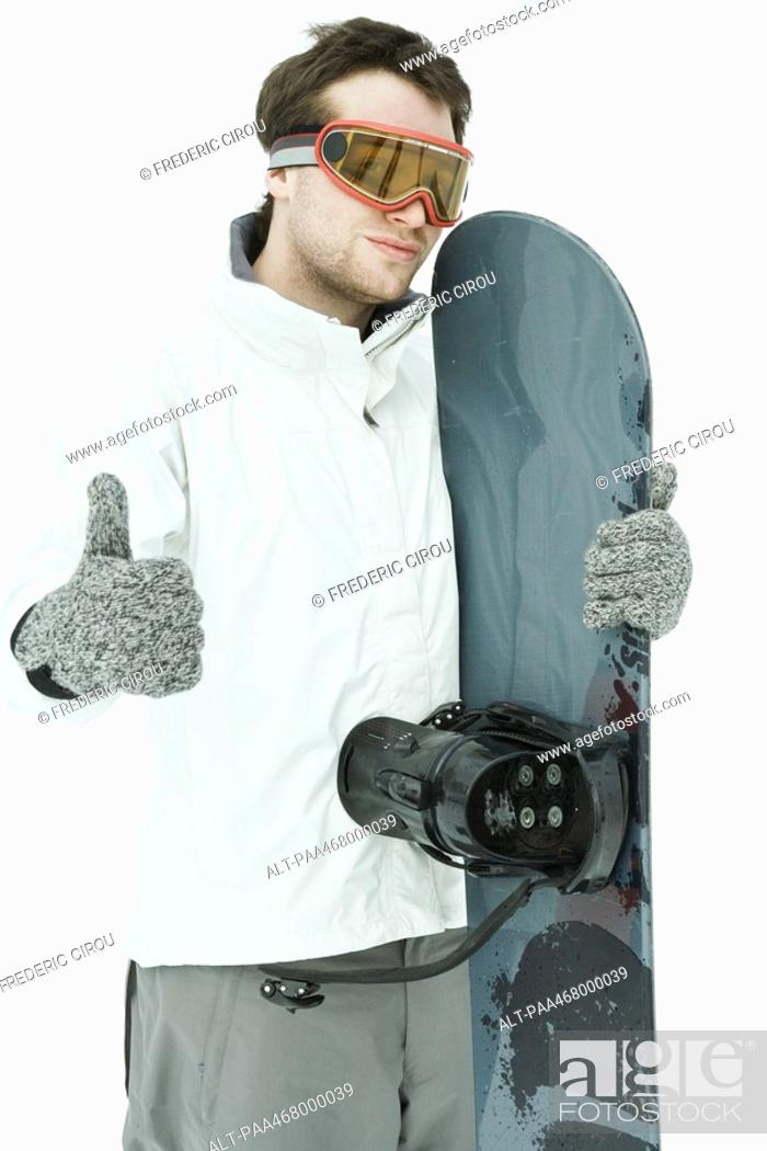 Stock Photo: Young male snowboarder, giving thumbs up sign to camera.