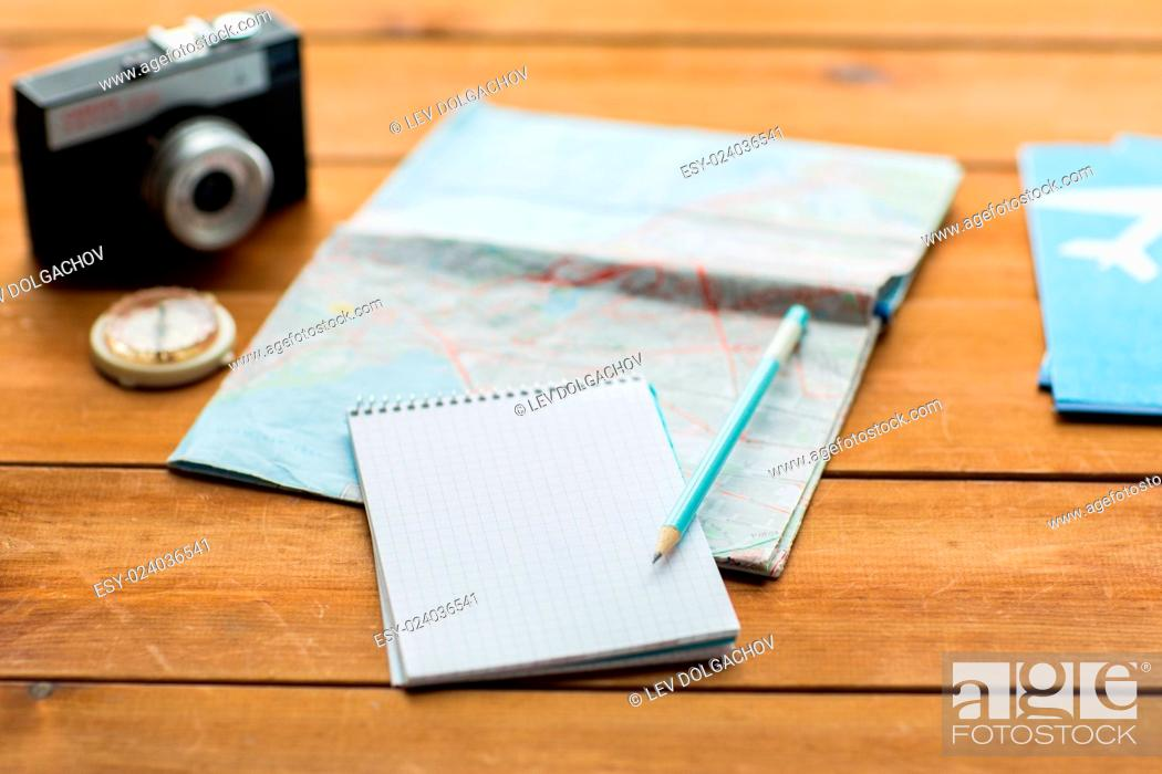 Stock Photo: vacation, tourism, travel and objects concept - close up of blank notepad with map and airplane tickets.