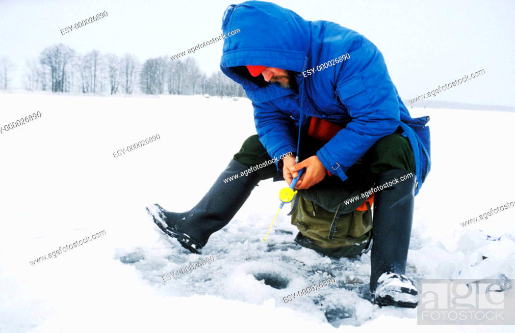 Stock Photo: A man is fishing on the ice of River Dalalven in Sweden.