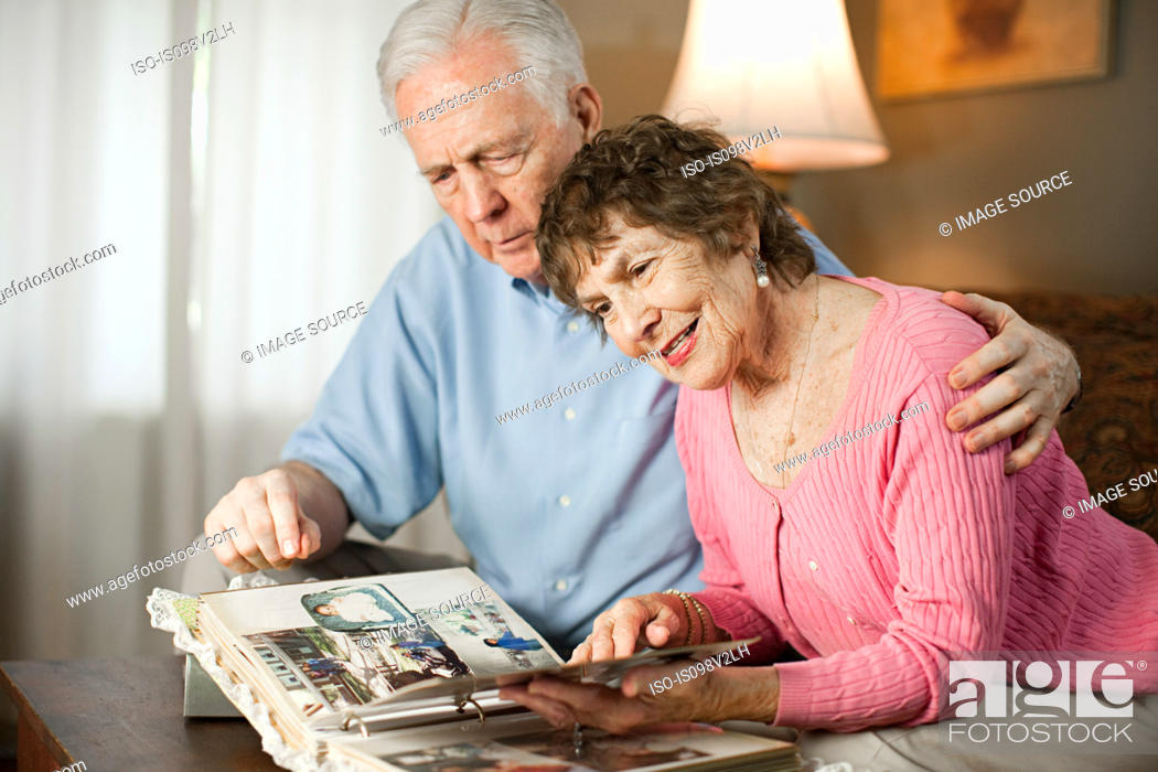 Stock Photo: Senior couple looking at family album.