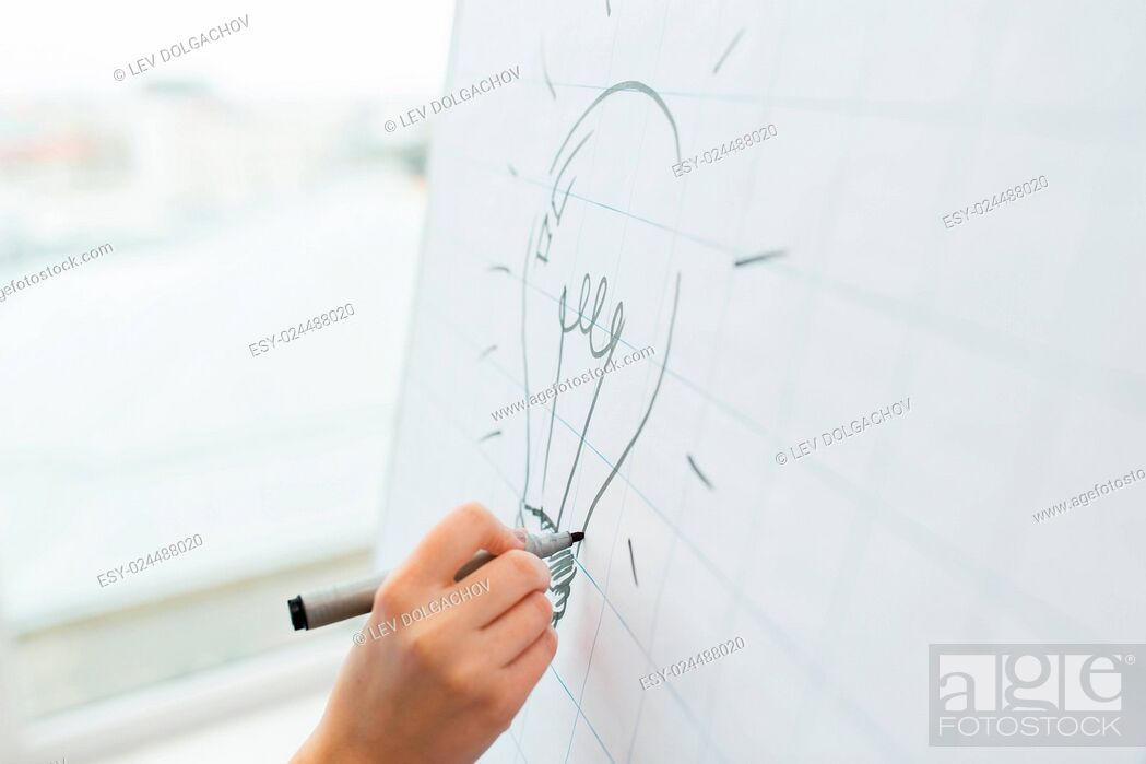 Stock Photo: business, people, idea, startup and education concept - close up of hand with marker drawing light bulb on flip chart at office.