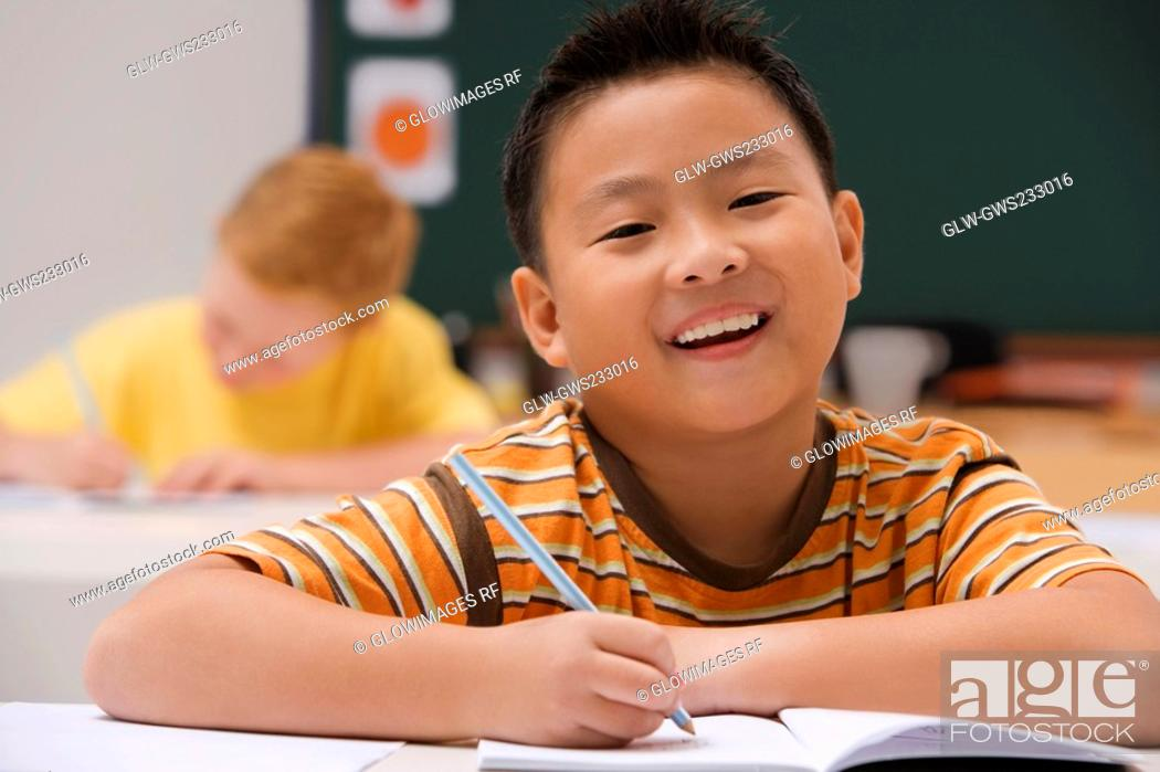 Stock Photo: Portrait of a schoolboy writing on a notebook with a pencil and smiling.
