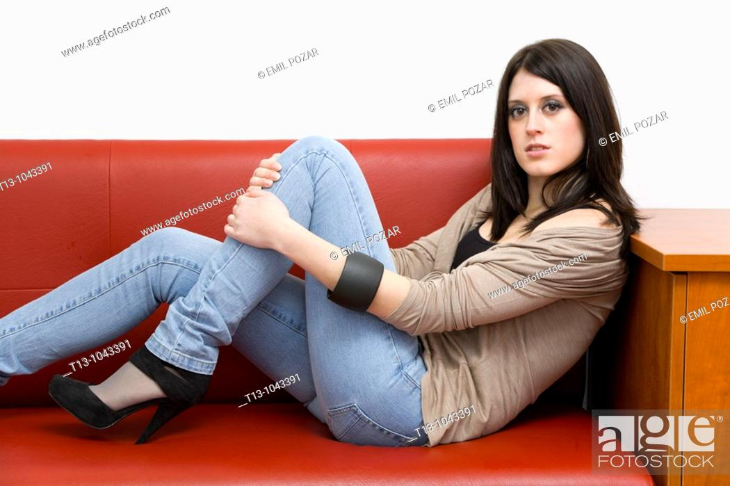 Stock Photo: Lounging on a Red sofa pretty young woman.