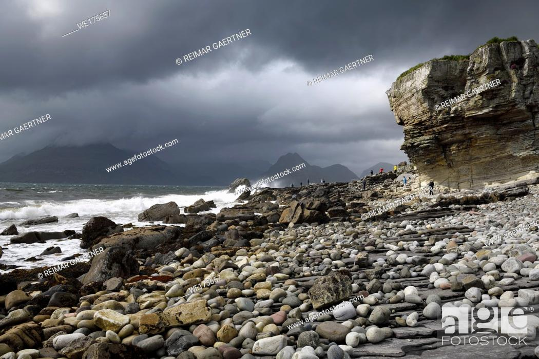 Stock Photo: Tourists on rocks of Elgol beach at Port na Cullaidh with Red Cuillin Mountains under clouds on Loch Scavaig Isle of Skye Scotland UK.