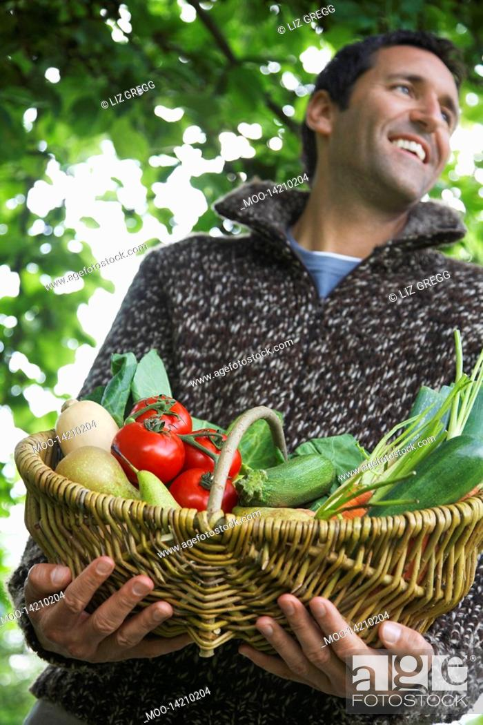 Stock Photo: Man holding fruit and vegetable basket outdoors.