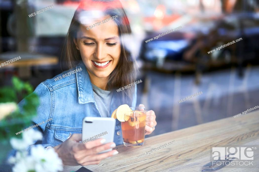 Stock Photo: Smiling young woman using phone and drinking tea in cafe.