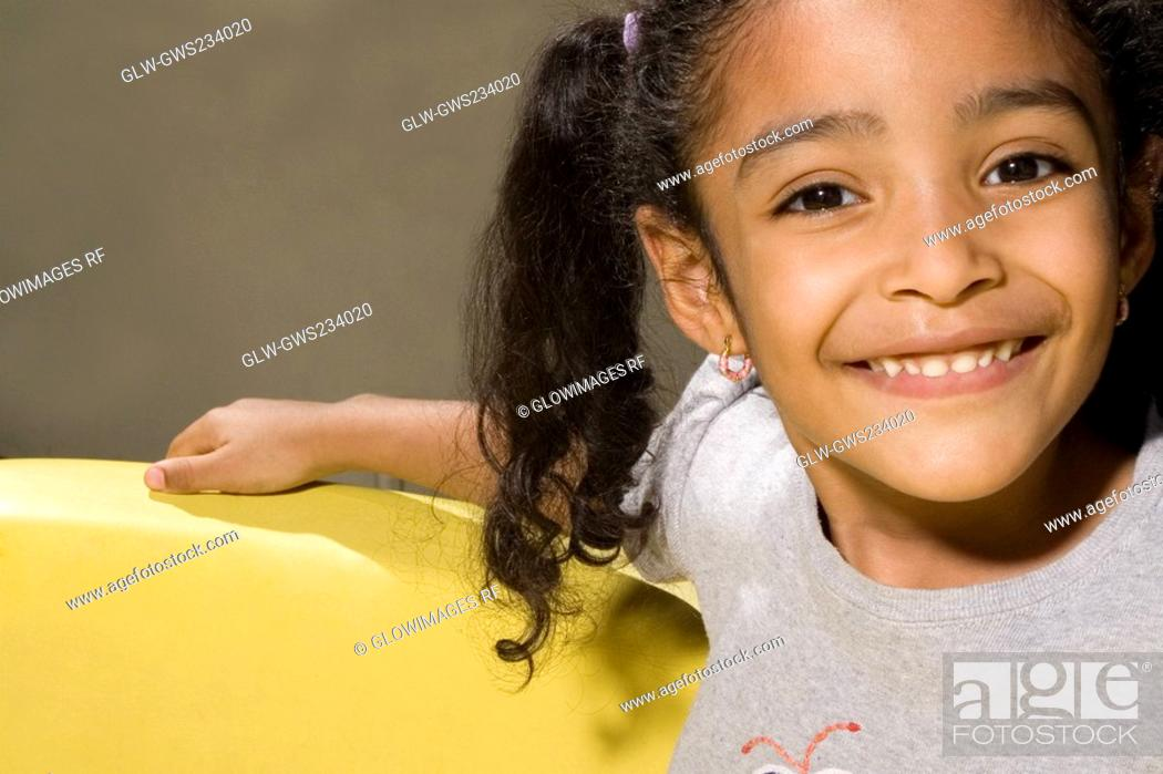 Stock Photo: Portrait of a girl in a toy car and smiling.