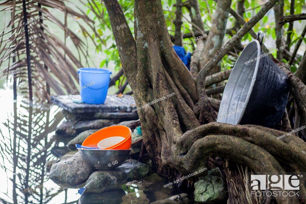 Stock Photo: Guatemala, Rio Dulce, pots by water.