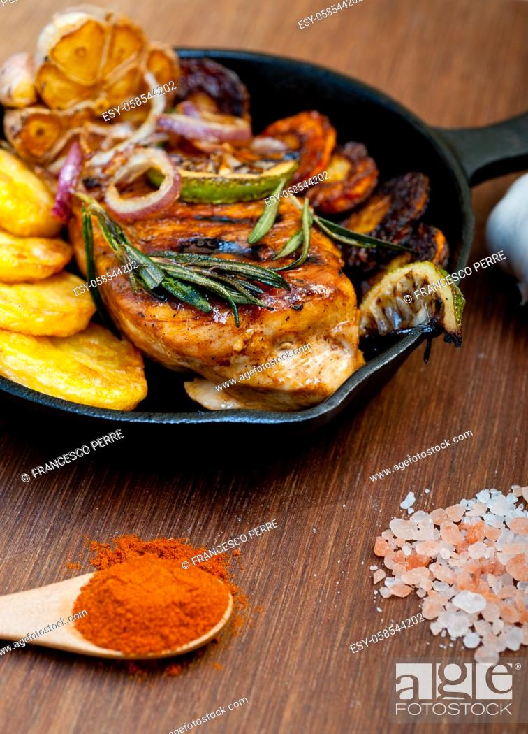 Stock Photo: roasted grilled BBQ chicken breast with herbs and spices rustic style on iron skillet.