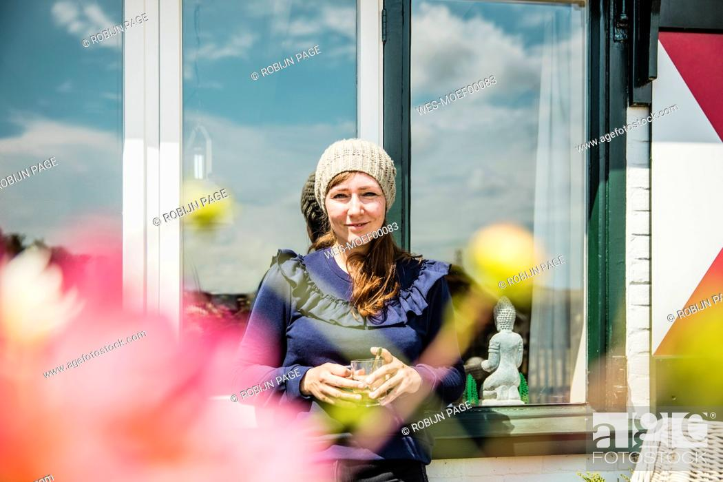 Photo de stock: Portrait of smiling woman at a window.