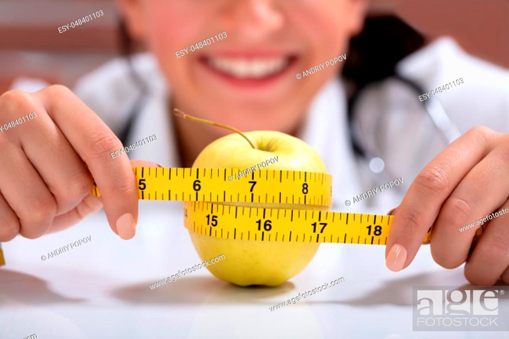 Stock Photo: Close-up Of Female Dietitian Measuring The Whole Apple With Measuring Tape On Desk.