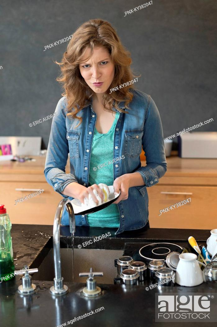 Stock Photo: Woman washing dishes in the kitchen.